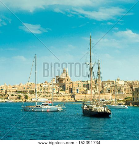picturesque view of sailing boats with Valletta cityscape on the background, Malta