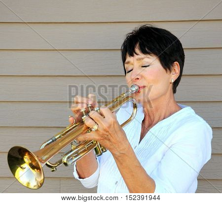 Mature female jazz trumpet player blowing her horn outside.