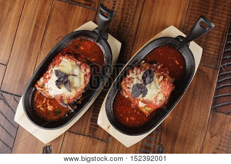 Baked zucchini and eggplant with tomato sauce in a pan. Wooden background.