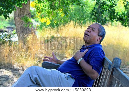 African american male having chest pains while sitting outside on a park bench.