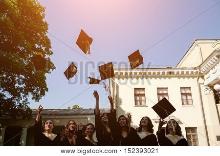 group of happy graduates throwing graduation hats in the air celebrating