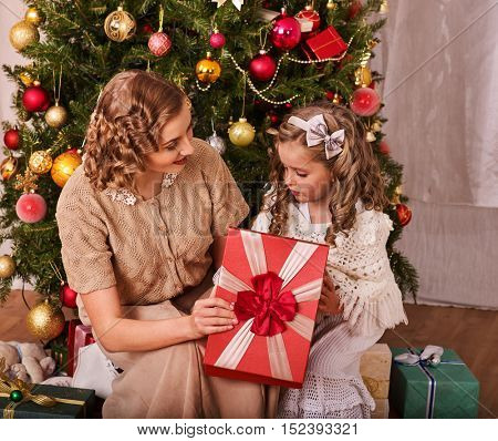 Child with mother receiving near Christmas tree. Mom gives daughter gift box with red bow.