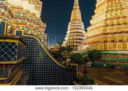 The beautifully decorated pagodas of Wat Pho temple at night. Bangkok, Thailand. Traditional religious architecture of Asia.