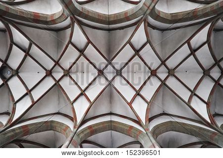 Arched ceiling of gothic church. Stone frame and white filling. Symmetrical form look up.