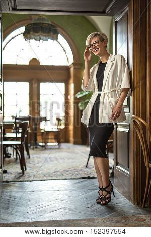 Happy blonde girl with smile in glasses stands in the doorway in the hall of the restaurant. She looks to the side and holds glasses with right hand. Woman wears black dress and sandals, white coat.