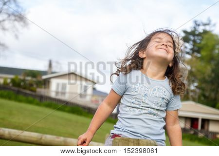 happy child girl enjoying being outdoors on natural background