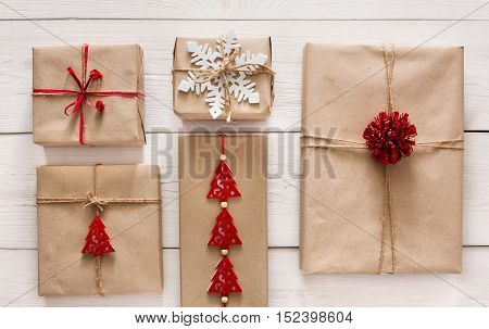 Christmas holiday handmade presents in craft paper with twine ribbon background. Boxes with bows and snowflakes on white wooden table, top view.