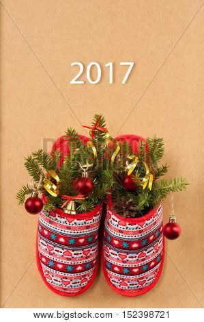 Christmas Fir-Tree With Decorative Balls In Red Slippers With Patterns On Wooden Background. Christmas Tree With Decorations In Slippers. Christmas Composition.