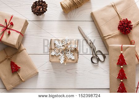 Christmas holiday handmade present in craft paper with twine ribbon. Making bow at xmas gift box, decorated with snowflake. Scissors on white wooden table, top view.