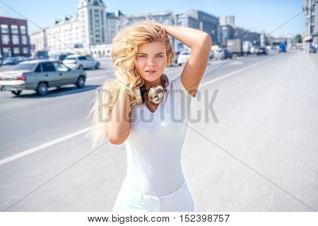 Beautiful young woman with music headphones on her neck standing against urban city background and looking straight to the camera.