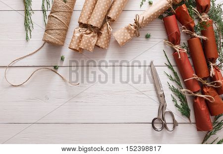 Wrapping gifts background. Handmade christmas present or garland candies from maroon paper with craft rope. Top view of white wooden table, winter holidays decorations and ornaments, copy space