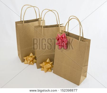 Three paper bag parcels and bows on white background