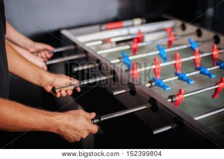 Group of friends having fun together playing table foosball