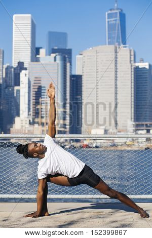 Young afro american man practicing yoga outdoors, in New York city.