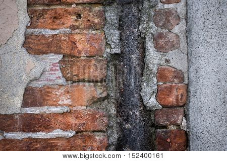 Antique wall with red old bricks, rusty metal and layers of plaster in Toulouse, France, closeup.
