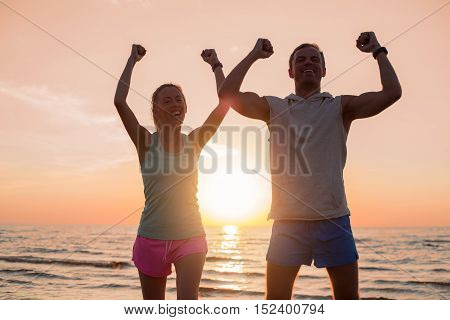 Couple with their hands up high standing in the sunset