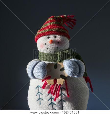 Vintage smiling plush snowman against blue background