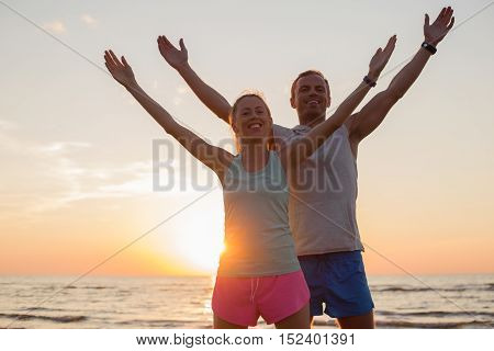 Fit couple stretching in sunset with their hands up high