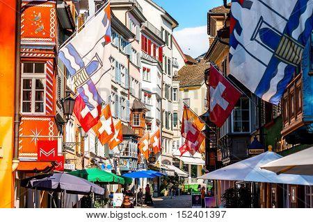 Zurich, Switzerland - June 28, 2016: Narrow street with swiss flags in the old town of Zurich city in Switzerland