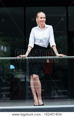 Full length portrait of a smiling businesswoman leaning on the glass railing outdoors