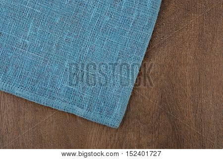 Napkin from left side wooden table. Soft blue woven linen fabric texture / wood texture. Coarse jute sack.  Top view background.
