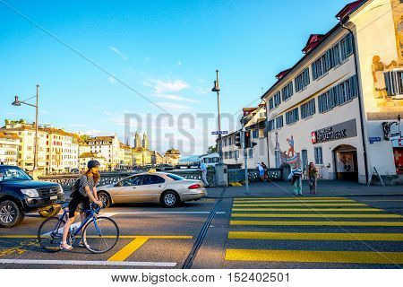 Zurich, Switzerland - June 28, 2016: Street view on Rudolf Brun bridge with cars, woman on the bicycle and people on the crossing in Zurich old town in Switzerland