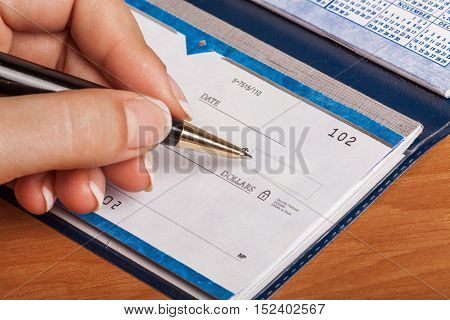 Woman's Hand Writing a Check - Close Up