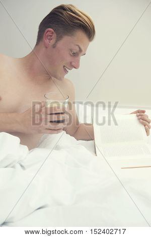 handsome blond man lying in bed and reading a book and holding a glass of coffee