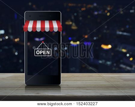 Modern smart mobile phone with on line shopping store graphic and open sign on wooden table over blur light city tower