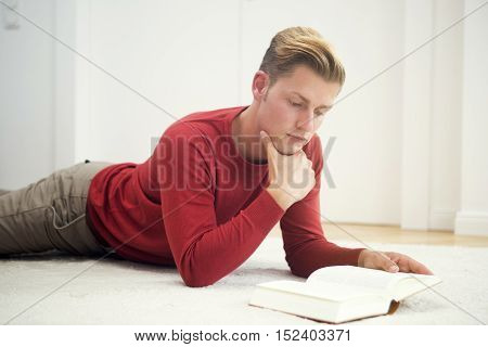 handsome blond man lying on carpet and reading a book