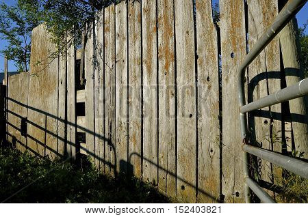 An old weathered wooden fence hosts shadows cast from a section of metal tubing from a gate.