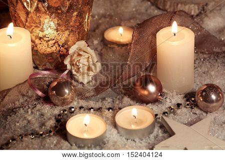 Christmas motif with candles on snow and a rose