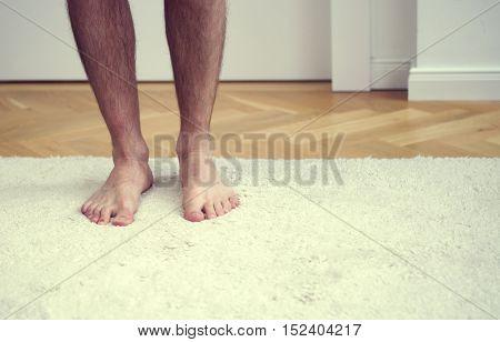 closeup of bare feet of man standing on white carpet