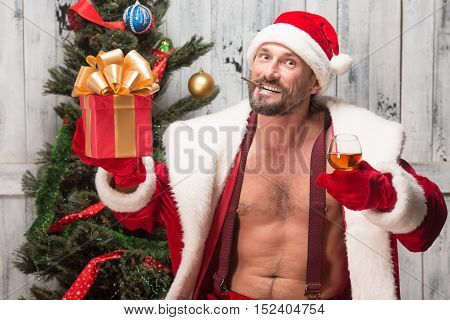 Portrait of happy bad Santa Clause smoking sigars, drinking alcohol drinks and looking at camera isolated on white background.