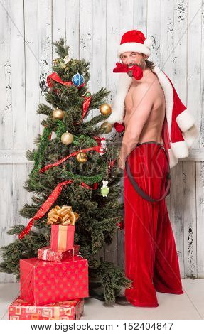 Angry bad Santa Clause posing naked near New Year Eve or tree while posing for photographer isolated on white background in studio.