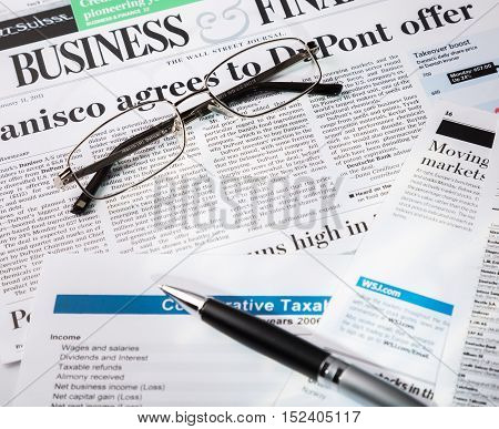 Glasses And Pen On Financial Reports And Newspaper Close-up