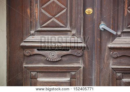 Old wooden door with the post box on it