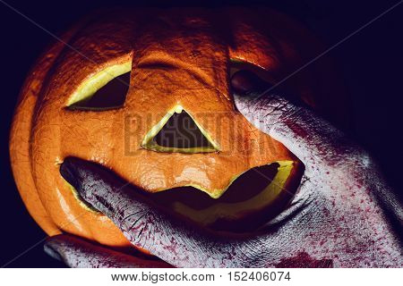 closeup of the scary hand of a monster or an undead man putting his fingers in the holes of a carved pumpkin
