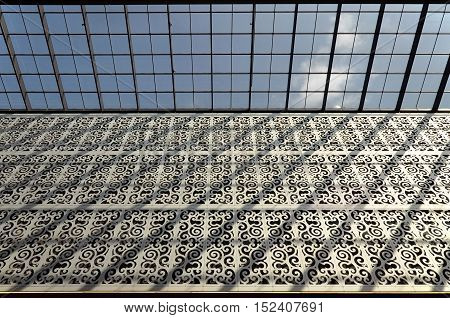 DRESDEN, GERMANY - APRIL 12, 2016: Interior of a modern shopping center. Patterned metal structure and a glass ceiling. Look up. Dresden, Saxony, Germany.