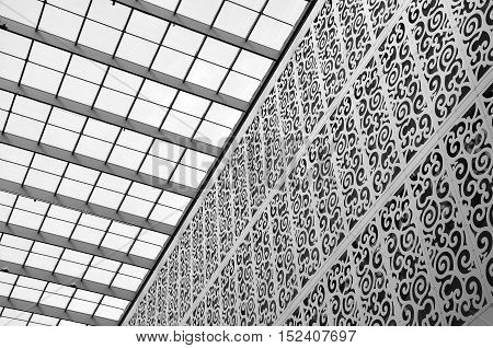 DRESDEN, GERMANY - APRIL 12, 2016: Interior of a modern shopping center. Patterned metal structure and a glass ceiling. Look up. Black and white. Dresden, Saxony, Germany.