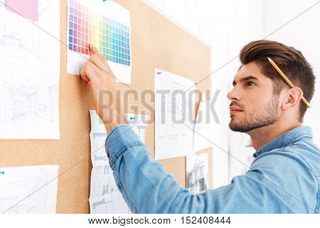 Serious young businessman pointing finger at the colorful template at the office board