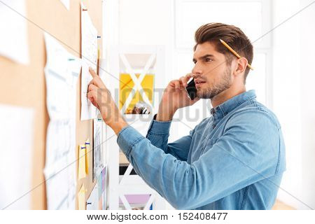 Close up portrait of a young concetrated casual businessman talking on the phone and pointing at board