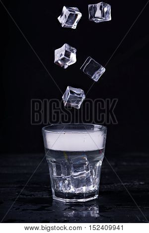 Hot water with a lot of steam in a glass and ice cubes in motion at a black background. Dark photo. Concept photo: three state of water - ice, water, steam.