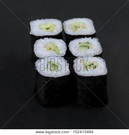 Cucumber nori rolls on a black background