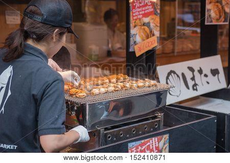 TOKYO  , JAPAN - OCTOBER 12 ,2016 : Tsukiji Market  , Tokyo, Japan. October 12 2016 Chefs are cooking grilled shell at Tsukiji market.