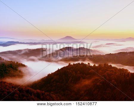 Filtered Photo. Autumn Hilly Landscape. Magnificent Autumn Creamy Fog