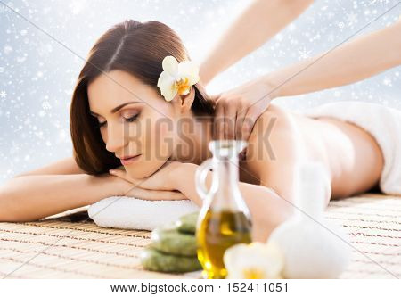 Young, healthy and beautiful girl relaxing in winter spa salon. Massage therapy, healing medicine and health care concept. Christmas background.