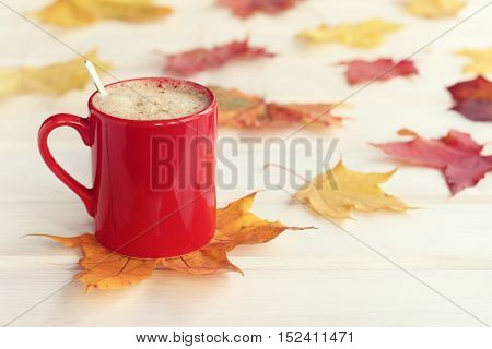 frothy cappuccino in a red mug with a spoon against the backdrop of autumn leaves / mood for coffee break