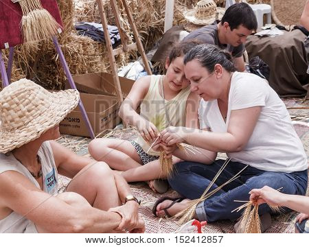 Woman Showing Girl How To Weave A Wreath Of Ears