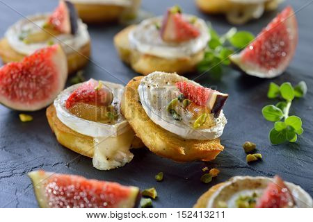 Baked spicy crostini appetizers with goat cheese, fig mustard, pistachios and fresh figs served on a slate board